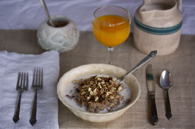 A bowl of oatmeal topped with Nina's granola, raw milk and maple syrup